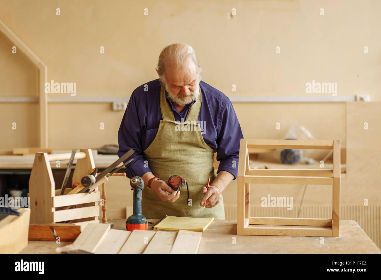 Alte Handwerker mit Maßband und etwas in der übung Buch Stockbild