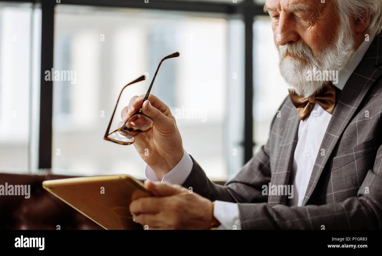 Alter Mann mit schlechtem Sehvermögen, die versuchen, ein Bild auf dem Bildschirm des Tablet auskundschaften Stockbild