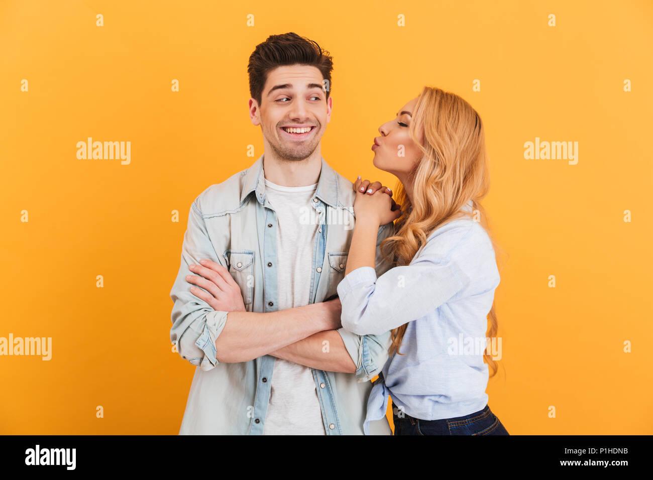 Portrait der junge schöne Menschen in der Kleidung zum Ausdruck bringt Liebe und Zuneigung, während Frau Mann Küssen auf die Wange über Gelb Hintergrund isoliert Stockbild