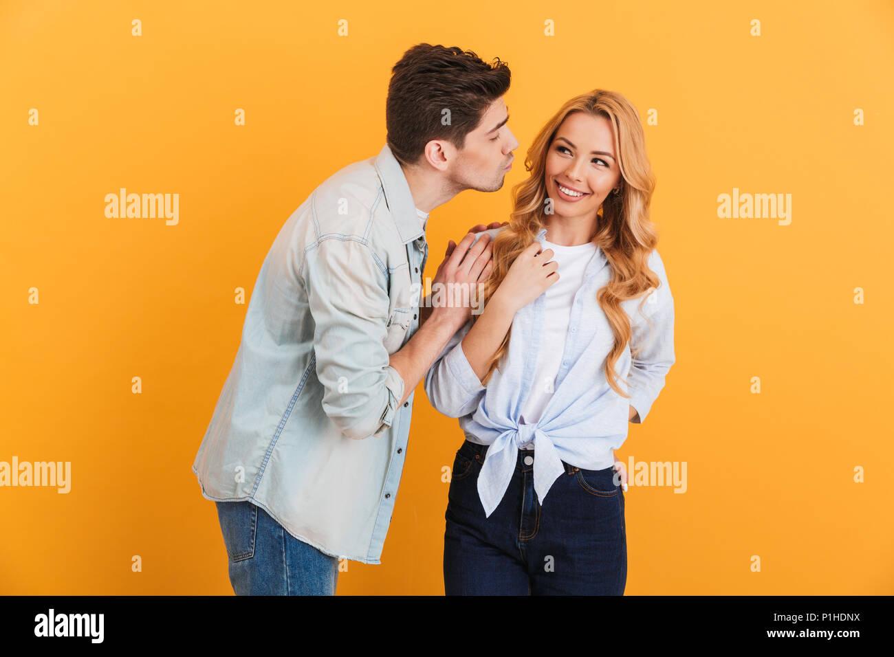 Image der jungen Menschen tragen Jeans Kleidung in Beziehung Liebe und Zuneigung, während Mann Frau Küssen auf die Wange über gelb Hinterg isoliert Stockbild