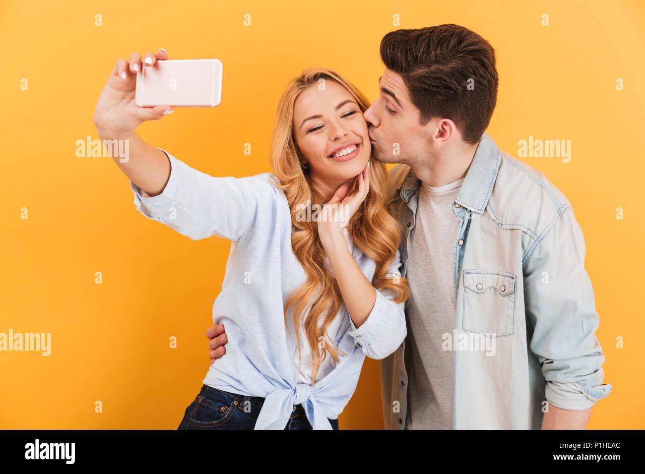 Portrait von Paar schöne unter selfie Foto auf Handy, während Mann Frau Küssen auf die Wange über Gelb Hintergrund isoliert Stockbild