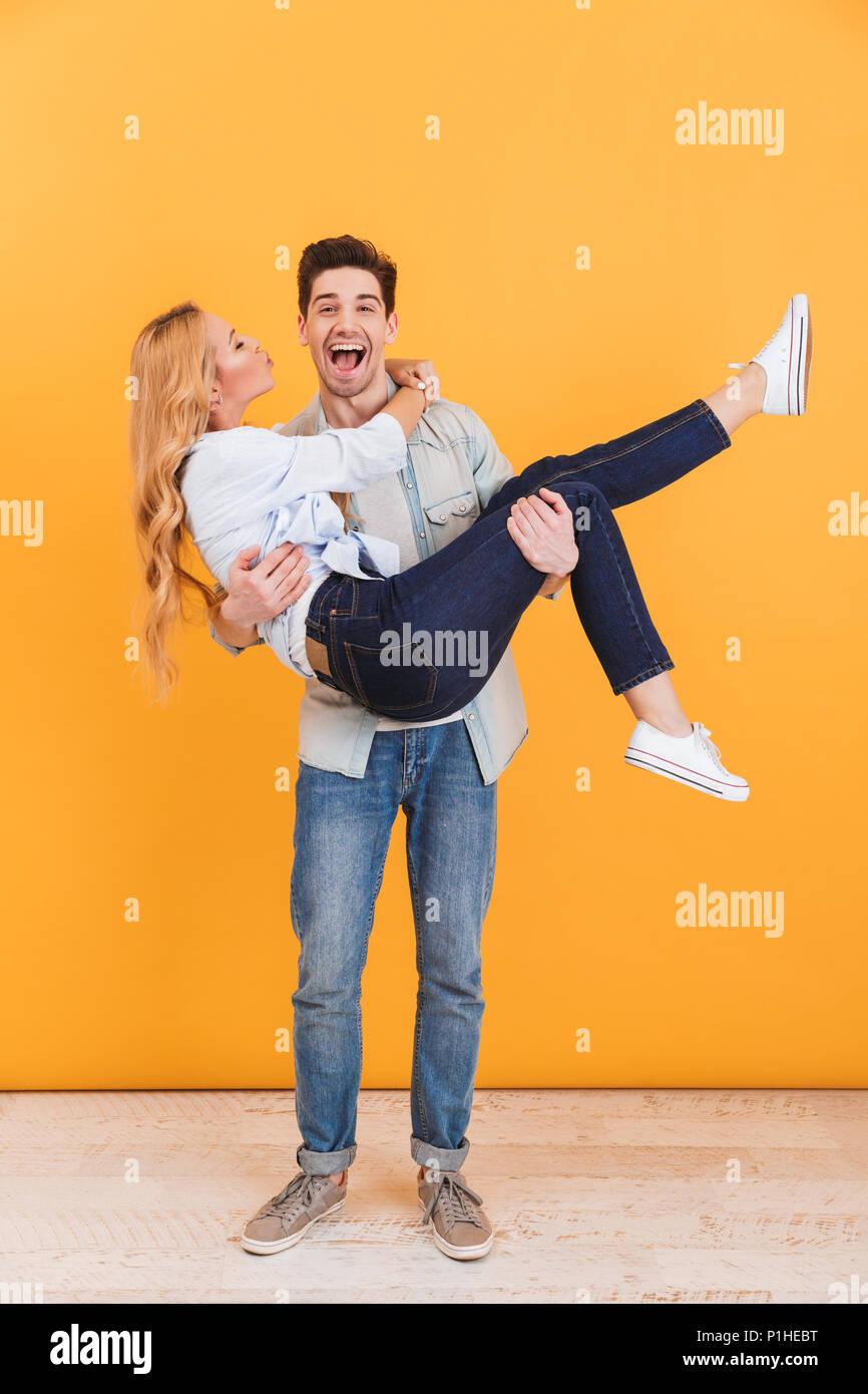 Volle Länge Foto von fröhlichen Menschen und lächelnd Frau in seinen Armen, der seine Wange, isoliert auf gelbem Hintergrund Stockbild