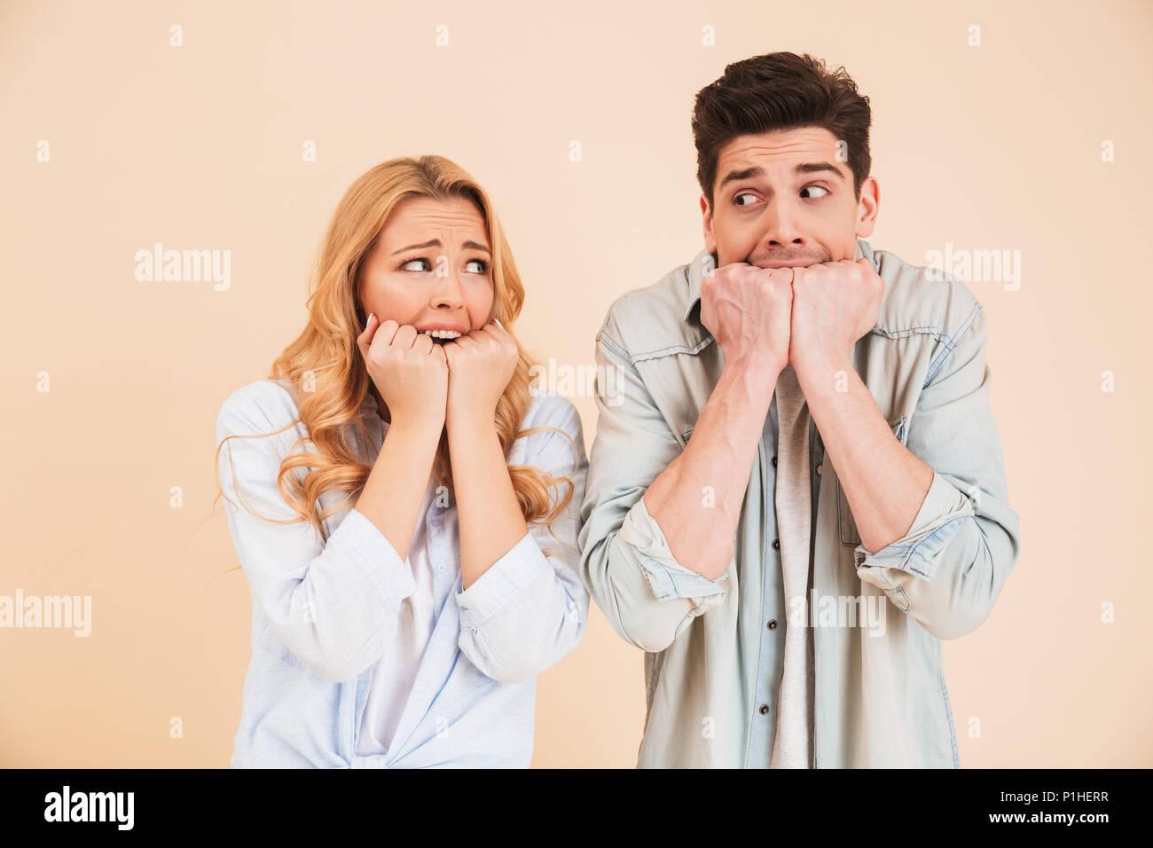 Bild von Angst, Mann und Frau in der Kleidung an einander suchen und Beißen ihre Fäuste emotional über beigen Hintergrund isoliert Stockbild