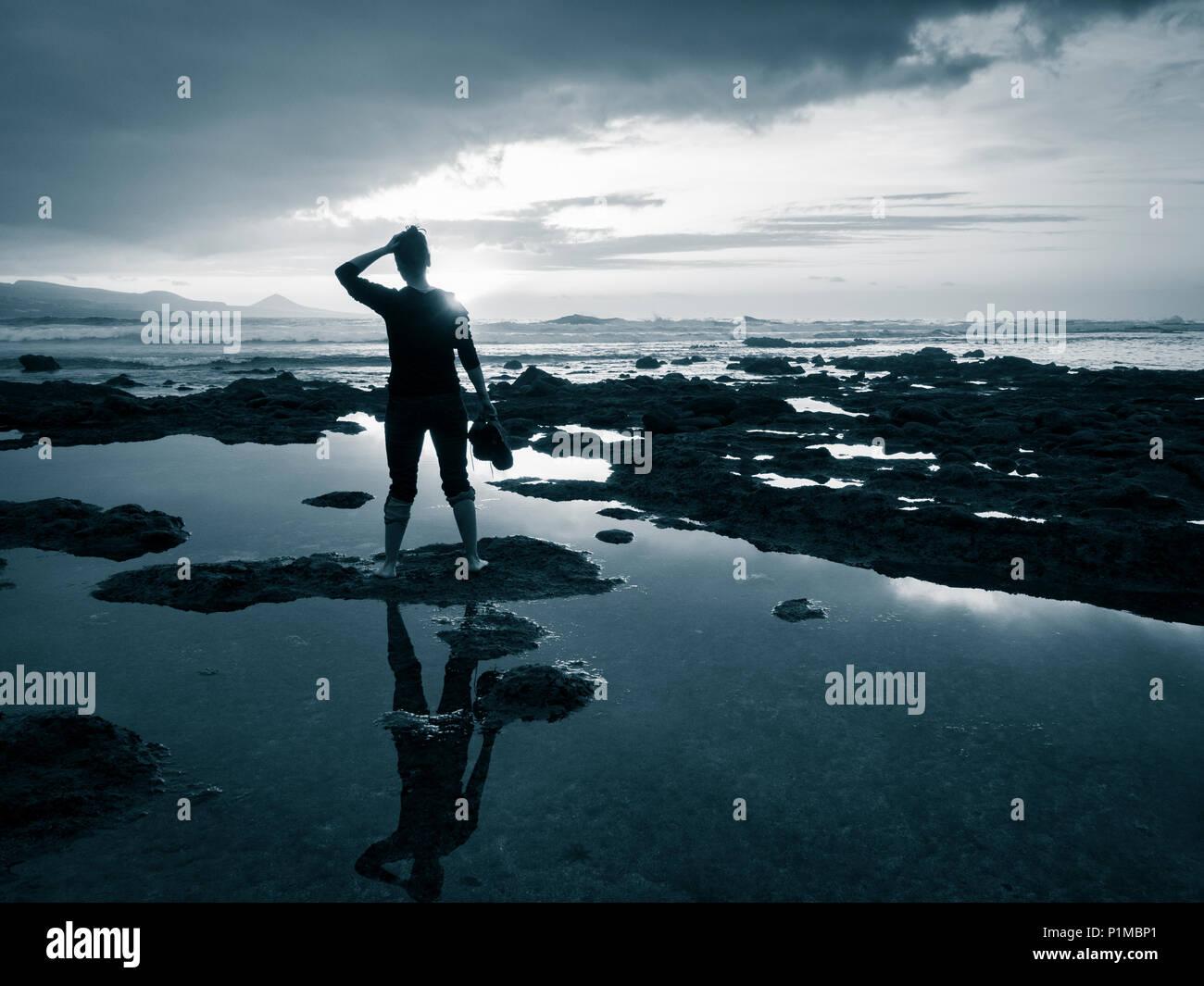 Ansicht der Rückseite des woman holding Schuhe mit Meerblick bei Sonnenuntergang: Meditation, psychische Gesundheit, Einsamkeit, Freiheit, Depression.. Konzept Bild Stockbild