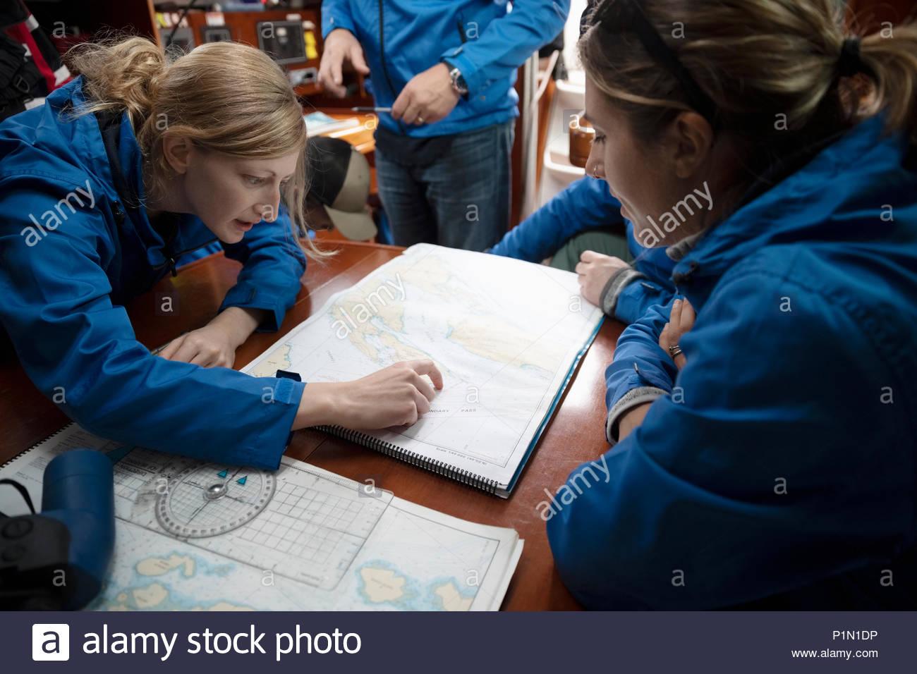 Sailing Team plotten Kurs an der Karte auf dem Segelboot Stockbild