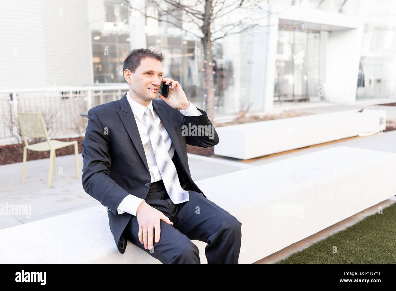 Witzig, wütend, irritiert, verwirrt Geschäftsmann sitzt auf der Bank, Gesicht sprechen Holding Smartphone Telefon Handy Handy in Anzug und Krawatte auf K. Stockbild