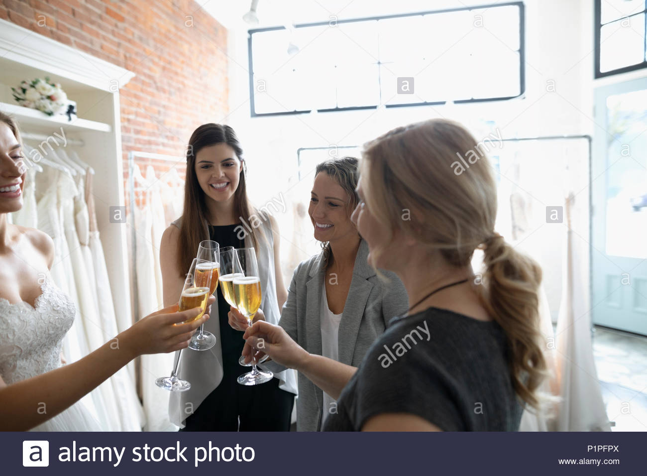 Braut, Mutter und Freunde toasten Champagner bei der Hochzeit Kleid Verschraubung am Bridal Boutique Stockbild