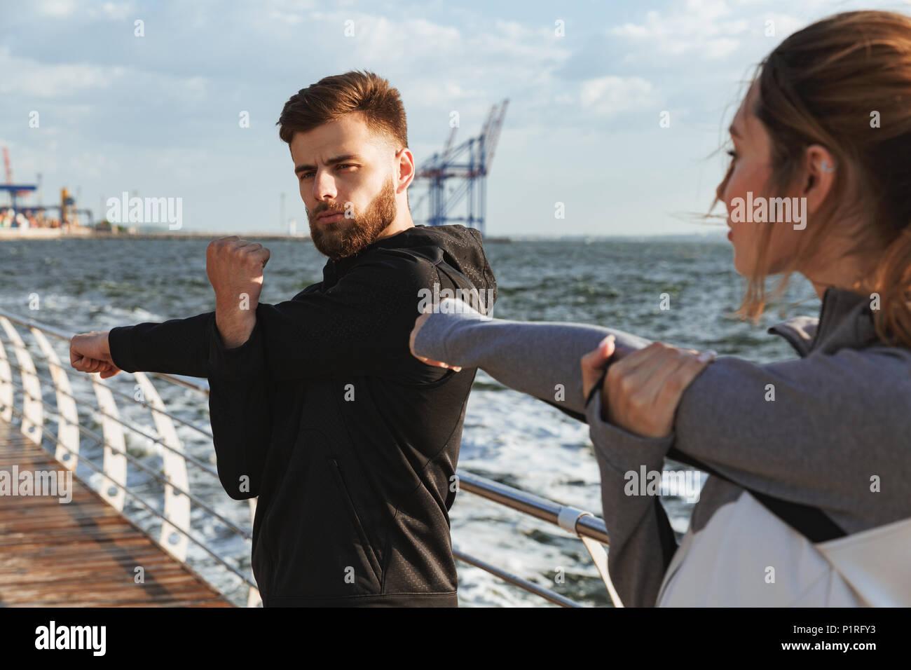 Junge sport Paar tun Dehnübungen vor dem Joggen am Strand konzentriert Stockfoto