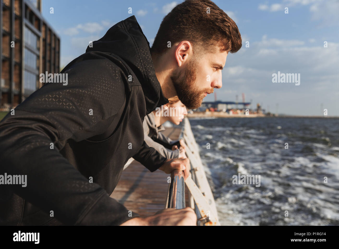 Nahaufnahme einer konzentrierten Fitness mann Aufwärmen am Strand mit einer Frau auf einem Hintergrund Stockbild