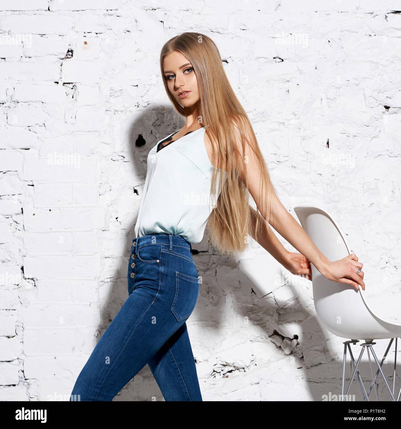 67e4f9cded9a5e Junge schöne Frau mit langen, geraden blondes Haar in Blue Jeans und hellen  Bluse stehend
