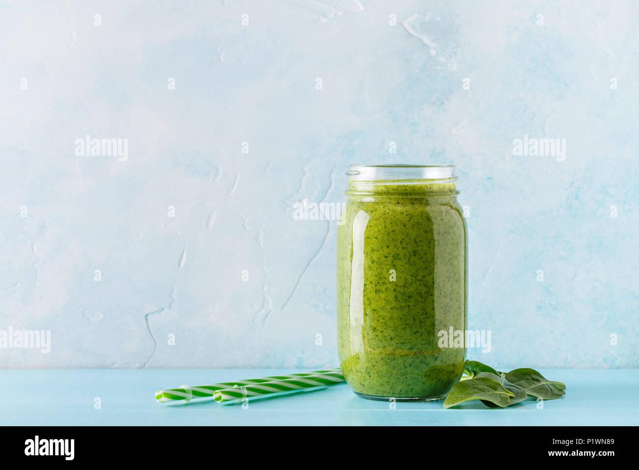 Grüne Smoothies/Saft in einem Glas auf einem blauen Hintergrund. Stockbild