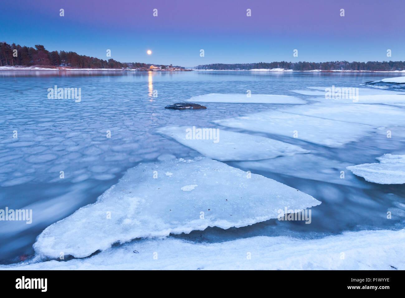 Aufgehenden Mond an einem kalten Winterabend am Oslofjord, im Ofen in Råde, Østfold Norwegen. Stockfoto