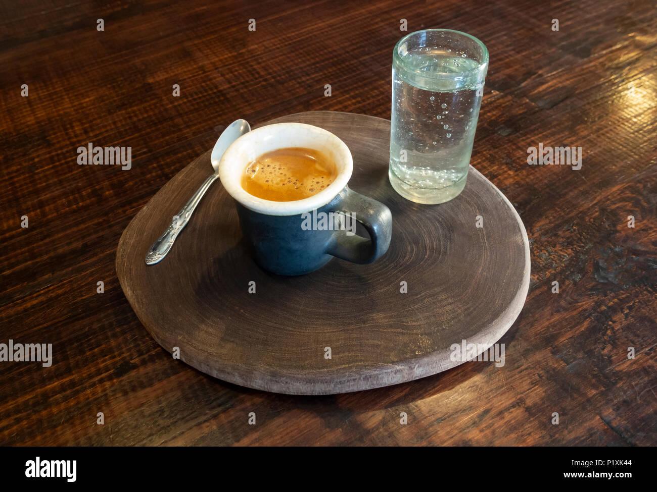 Eine Tasse Espresso mit einem kleinen Glas Wasser mit Kohlensäure Stockbild