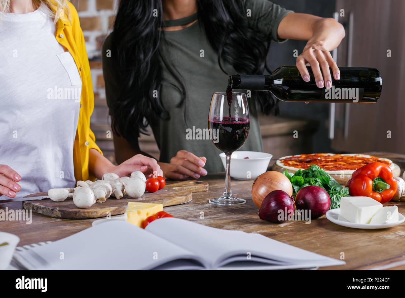 7/8 Schuß von Frauen trinken Wein beim Kochen Pizza zusammen Stockbild