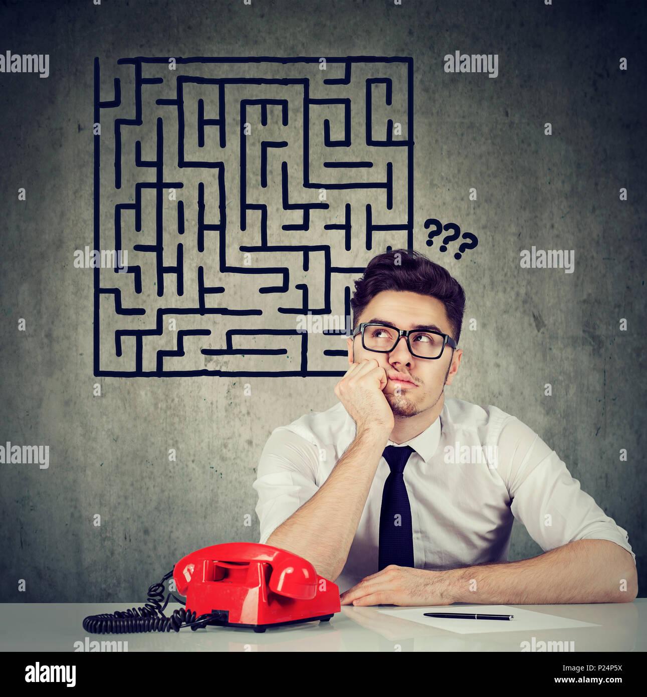 Verwirrt business Mann an Schreibtisch zum nächsten Schritt Fragen sitzen Stockbild