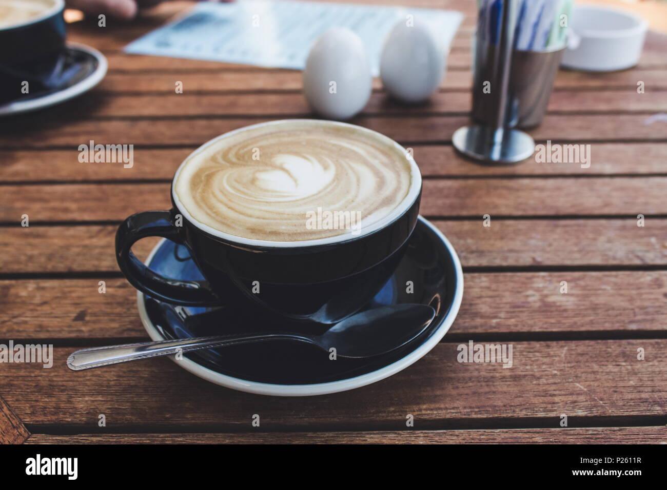 In der Nähe Bild von einer heißen Tasse Kaffee in einem schwarzen Schale Stockbild