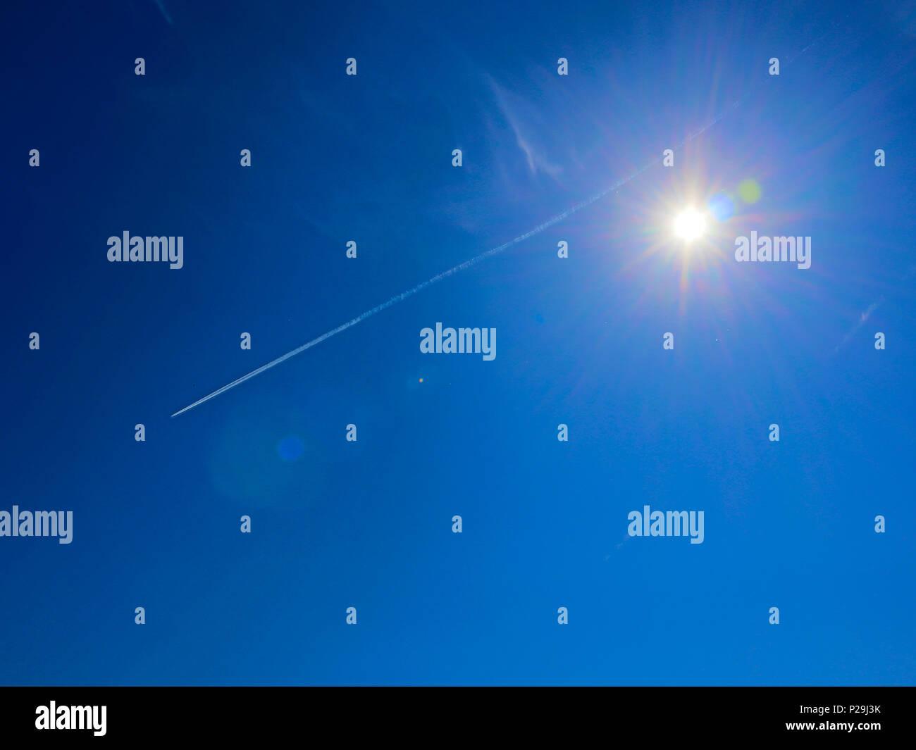 Helle Sonne mit Fackeln und spektrale Aureole um gegen den blauen Himmel mit weißen jet Spuren Stockbild