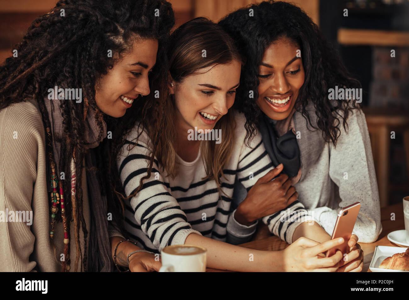 Drei Frauen in einem Restaurant mit Blick auf Handy sitzen und Lachen. Freunde sitzen in einem Café mit Kaffee und Snacks auf den Tisch mit einem m Stockbild
