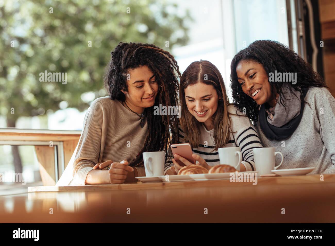 Drei Frauen sitzen in einem Restaurant am Handy suchen und lächelnd. Freunde in einem Café mit Kaffee und Snacks auf den Tisch in einem mo Suchen sitzen Stockbild