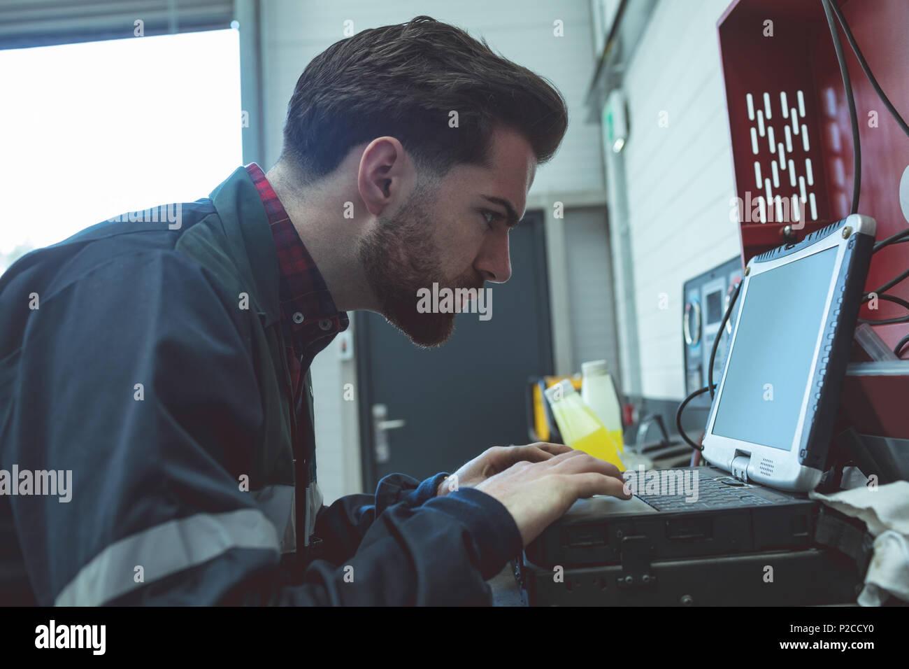 Aufmerksame Mechaniker mit Laptop Stockbild