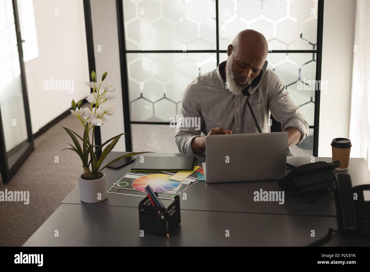 Senior Graphic Designer Gespräch am Handy am Schreibtisch Stockbild
