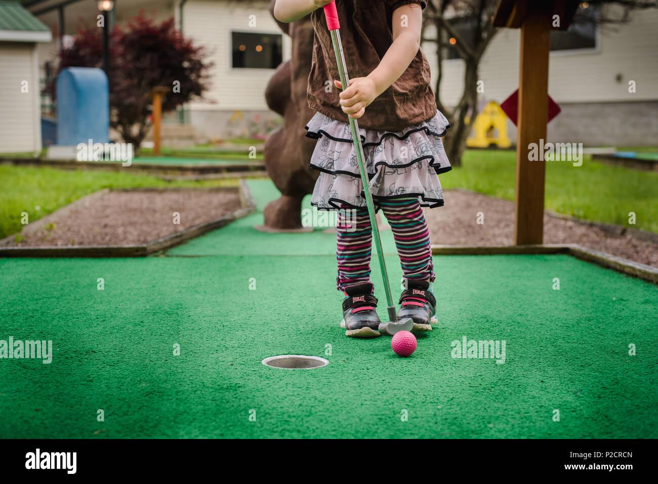 Ein junges Mädchen spielt Minigolf bei schönem Wetter. Stockbild