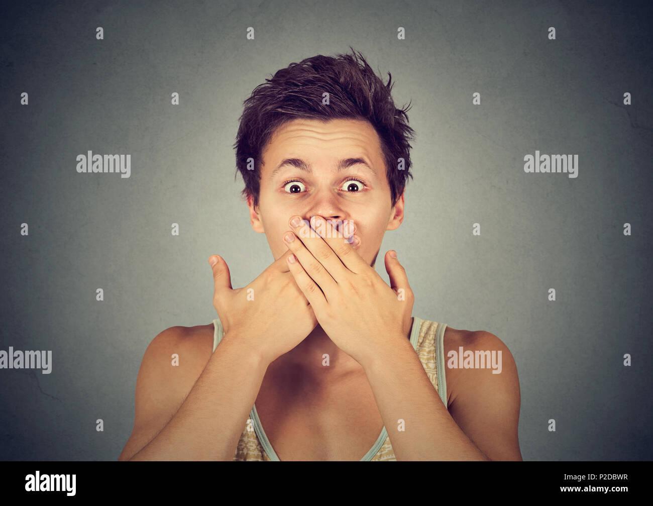 Junge betäubt Kerl für Mund mit beiden Händen suchen Angst zu sprechen, und wenn man die Kamera auf Grau Stockbild