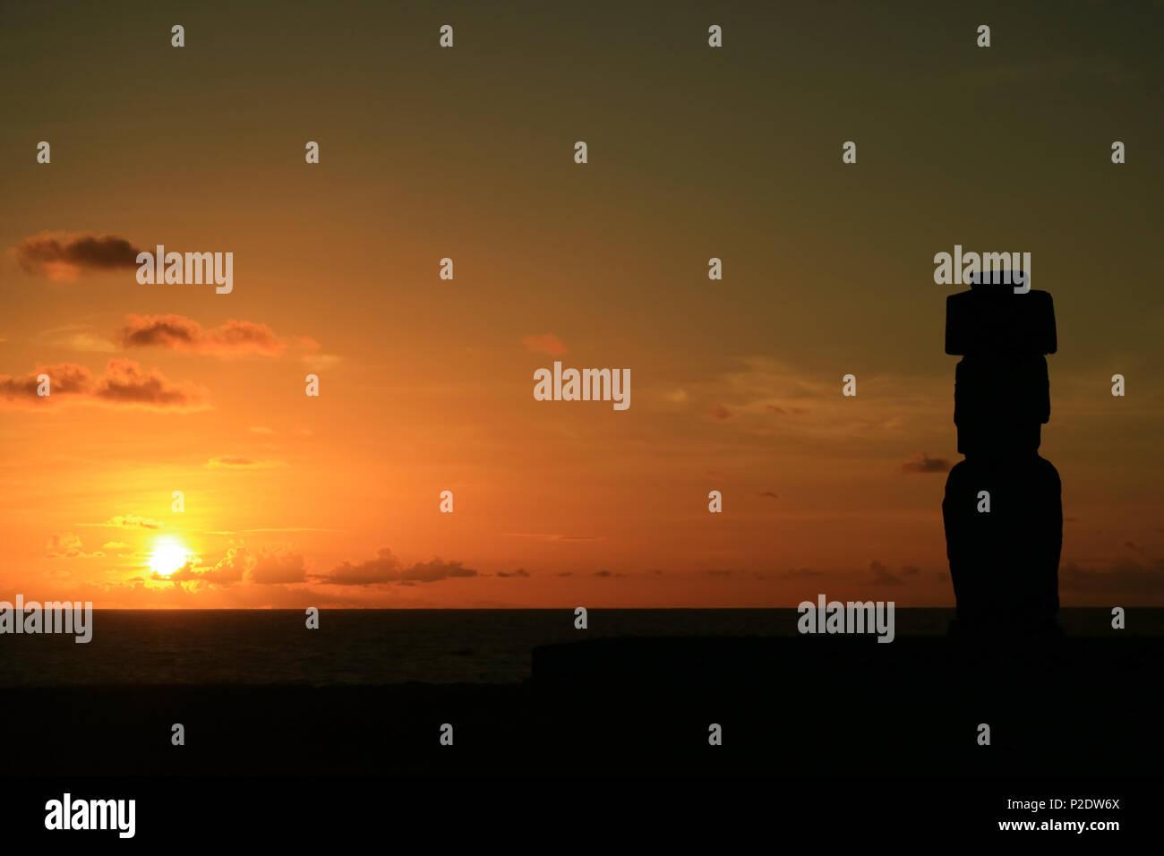 Atemberaubende Aussicht auf den Sonnenuntergang über dem Pazifischen Ozean mit der Moai Silhouette in der Ahu Tahai, Easter Island, Chile Stockbild