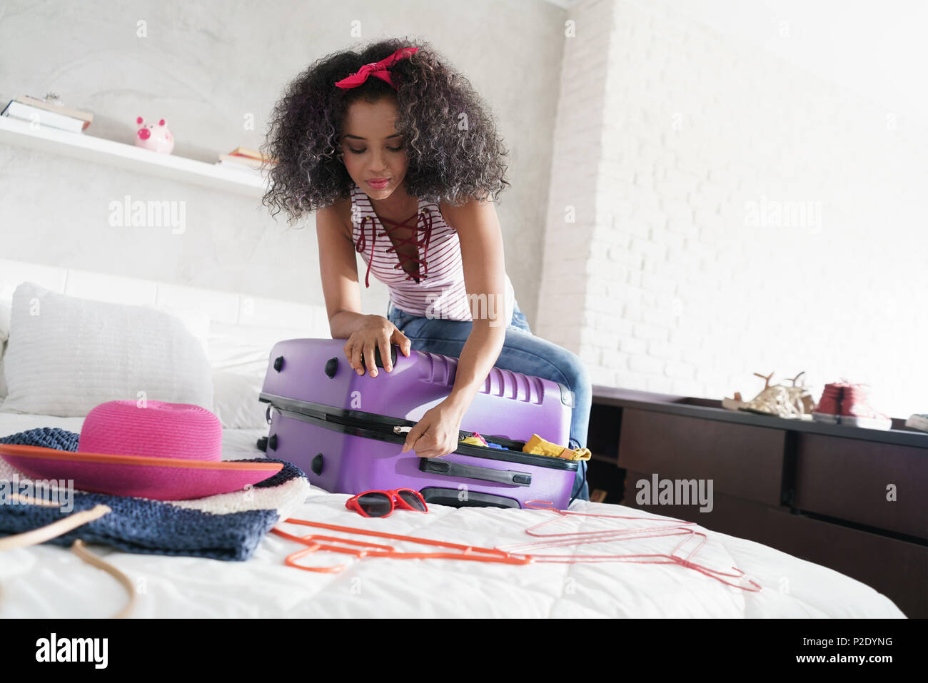 African American Girl Vorbereitung Gepäck für Urlaub und Reisen Stockbild
