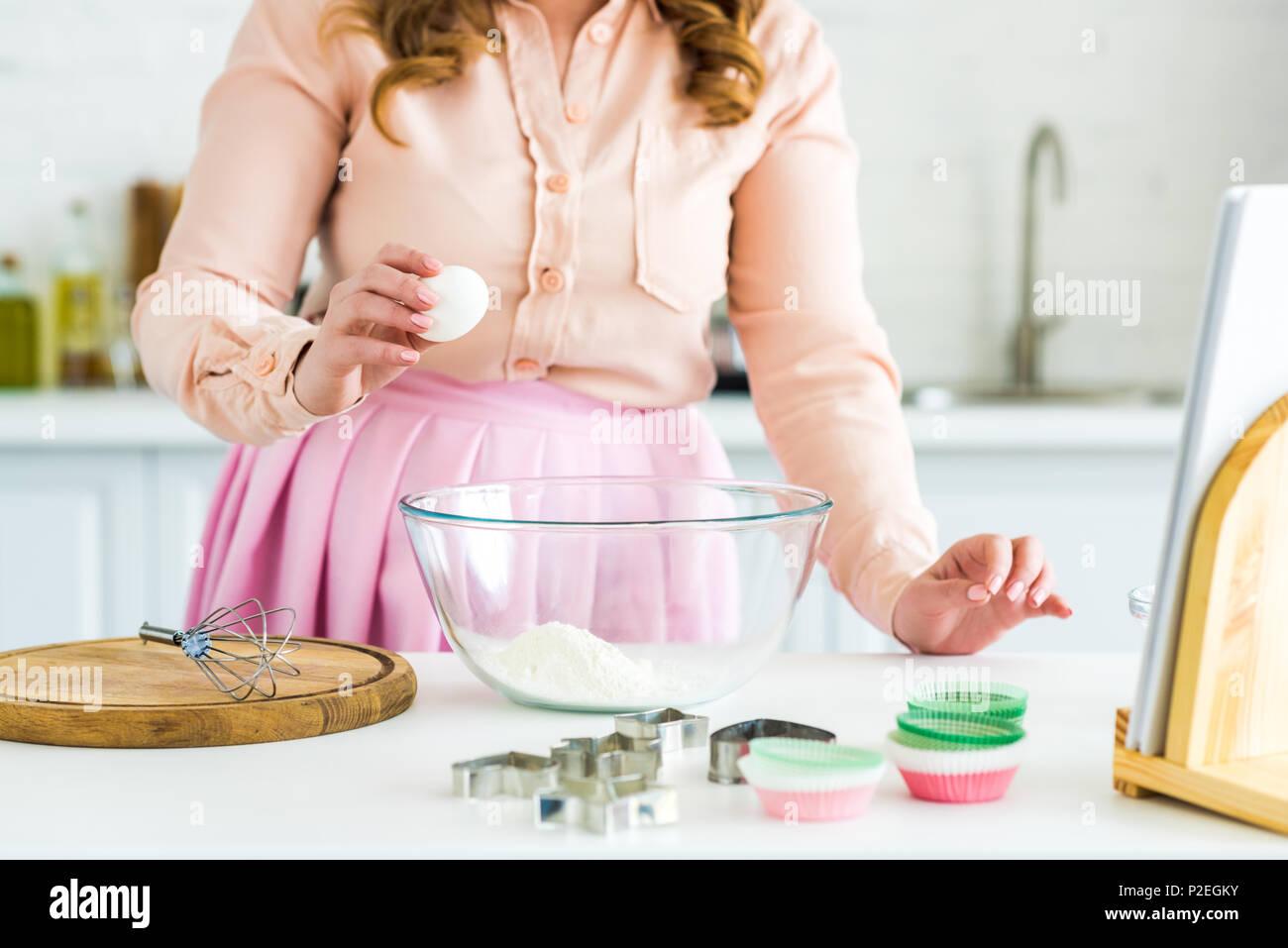 7/8 Bild der Frau, das Ei für den Teig in der Küche Stockbild