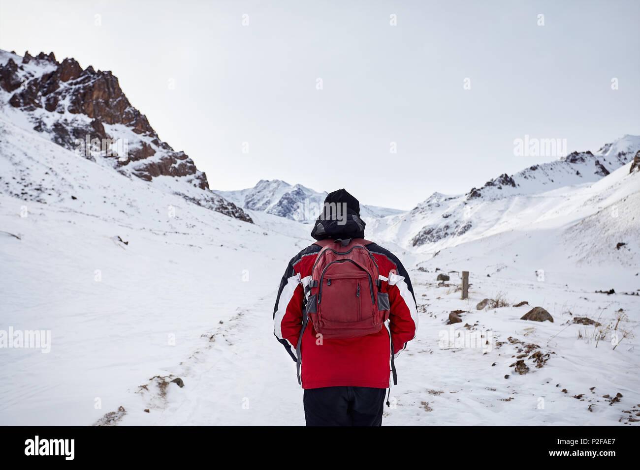 Wanderer mit roten Rucksack wandern rund um schneebedeckten Berge. Freiheit von trekking Konzept. Stockbild