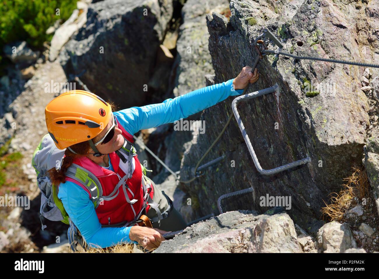 Klettersteig Kitzbühel : Frau aufsteigend bügeleisen krämpfe auf klettersteig