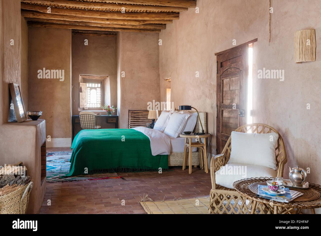 Rattan Sessel und Tisch im Vordergrund der Schlafzimmer mit ...