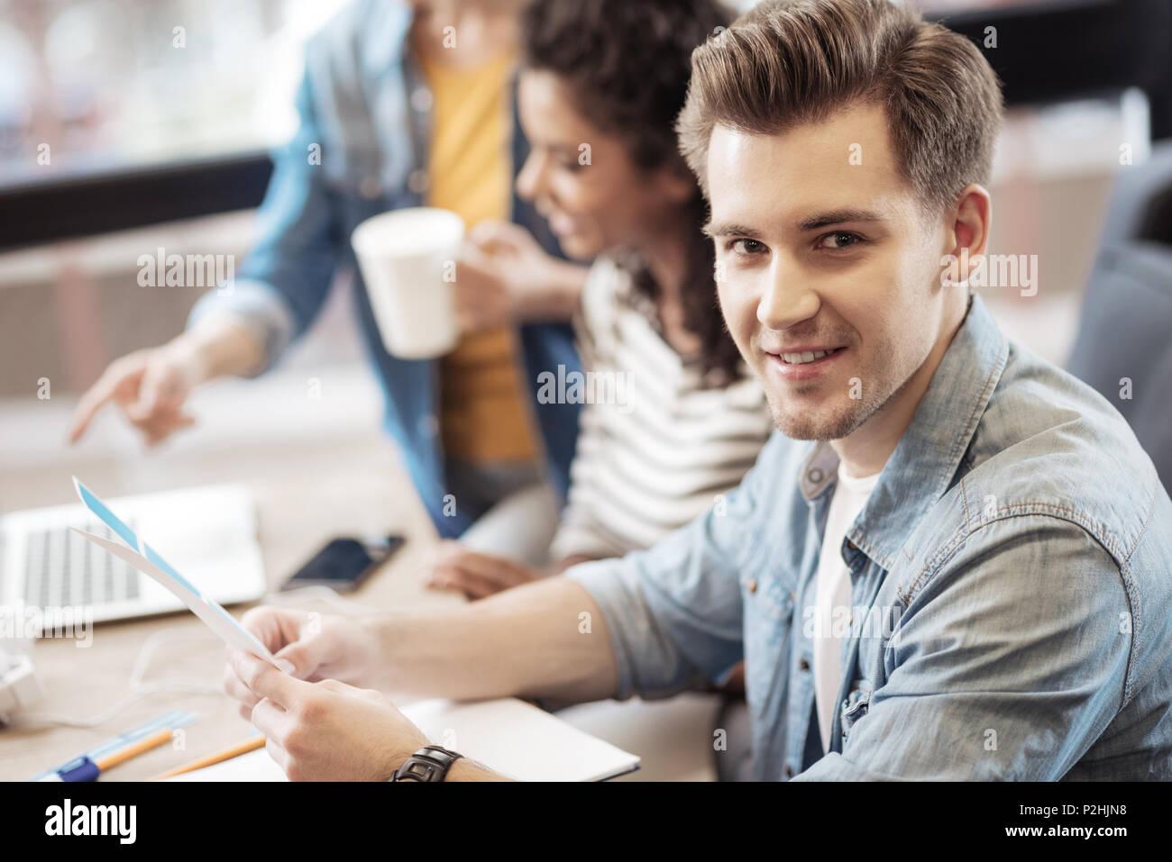 Fröhlicher junger Mann zu Ihnen schauen Stockbild