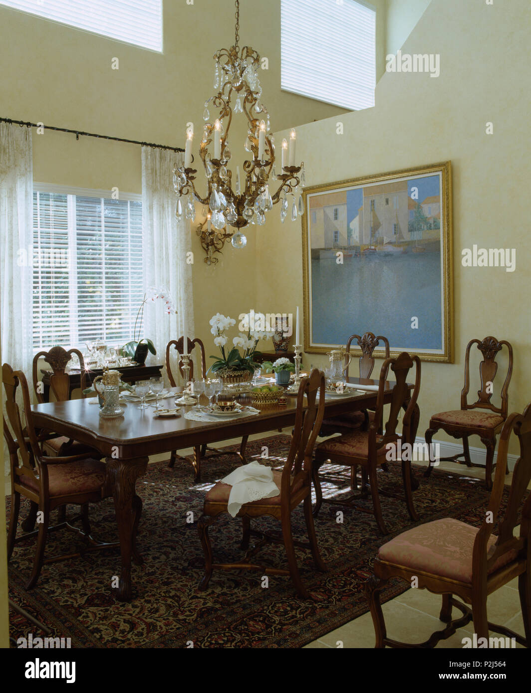 Beleuchtete Antiken Kronleuchter Aus Kristall Oben Mahagoni Tisch Und  Stühle In Doppelter Höhe Esszimmer Mit Großem Bild An Der Wand
