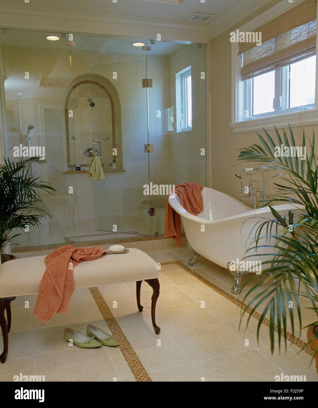Cremefarbenen Gepolsterten Hocker Und Freistehende Badewanne Im Modernen Bad  Mit Glastüren Auf Eine Große, Ebenerdige Dusche