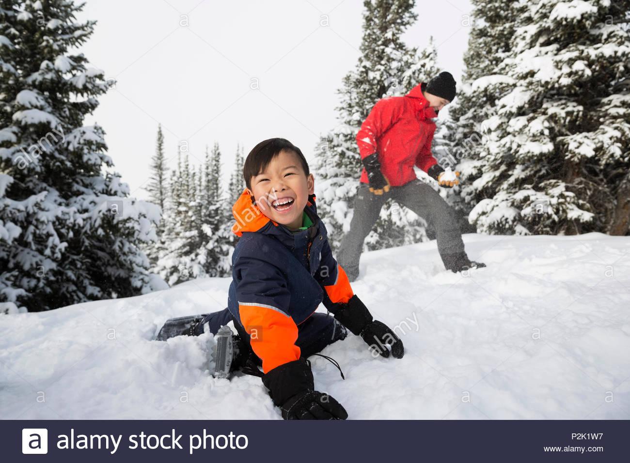 Glückliche, unbeschwerte Sohn genießen Schneeballschlacht mit Vater Stockbild