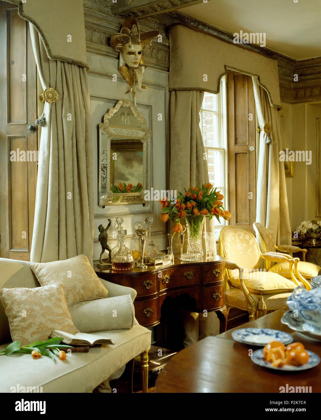 Venezianische Maske Und Spiegel An Der Wand Zwischen Hohen Fenstern Mit  Sahne Pelmets Und Vorhänge In Opulenten Land Wohnzimmer
