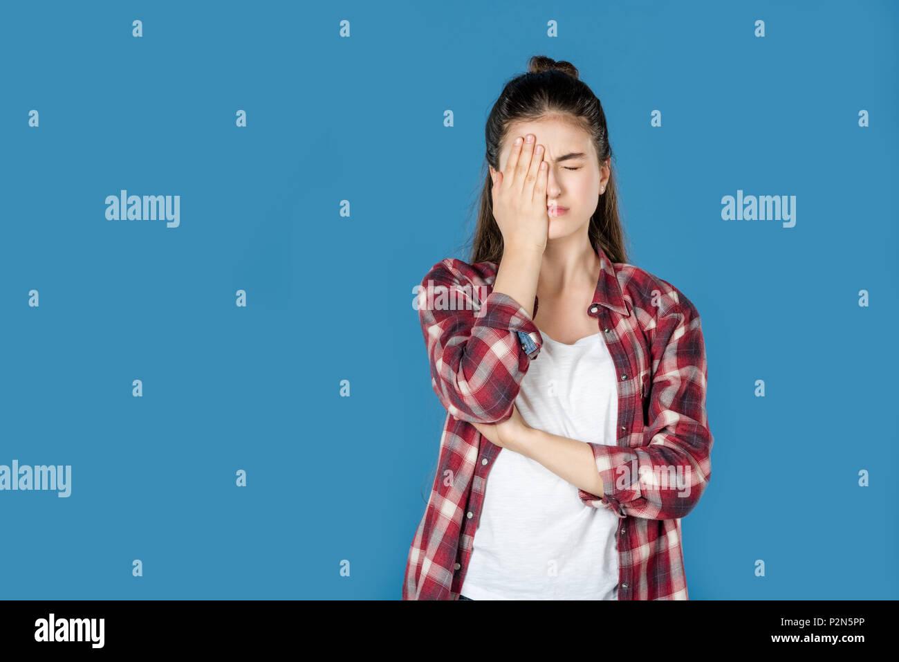 Beschämt jugendlich Mädchen die halbe Gesicht mit Hand isoliert auf Blau Stockbild