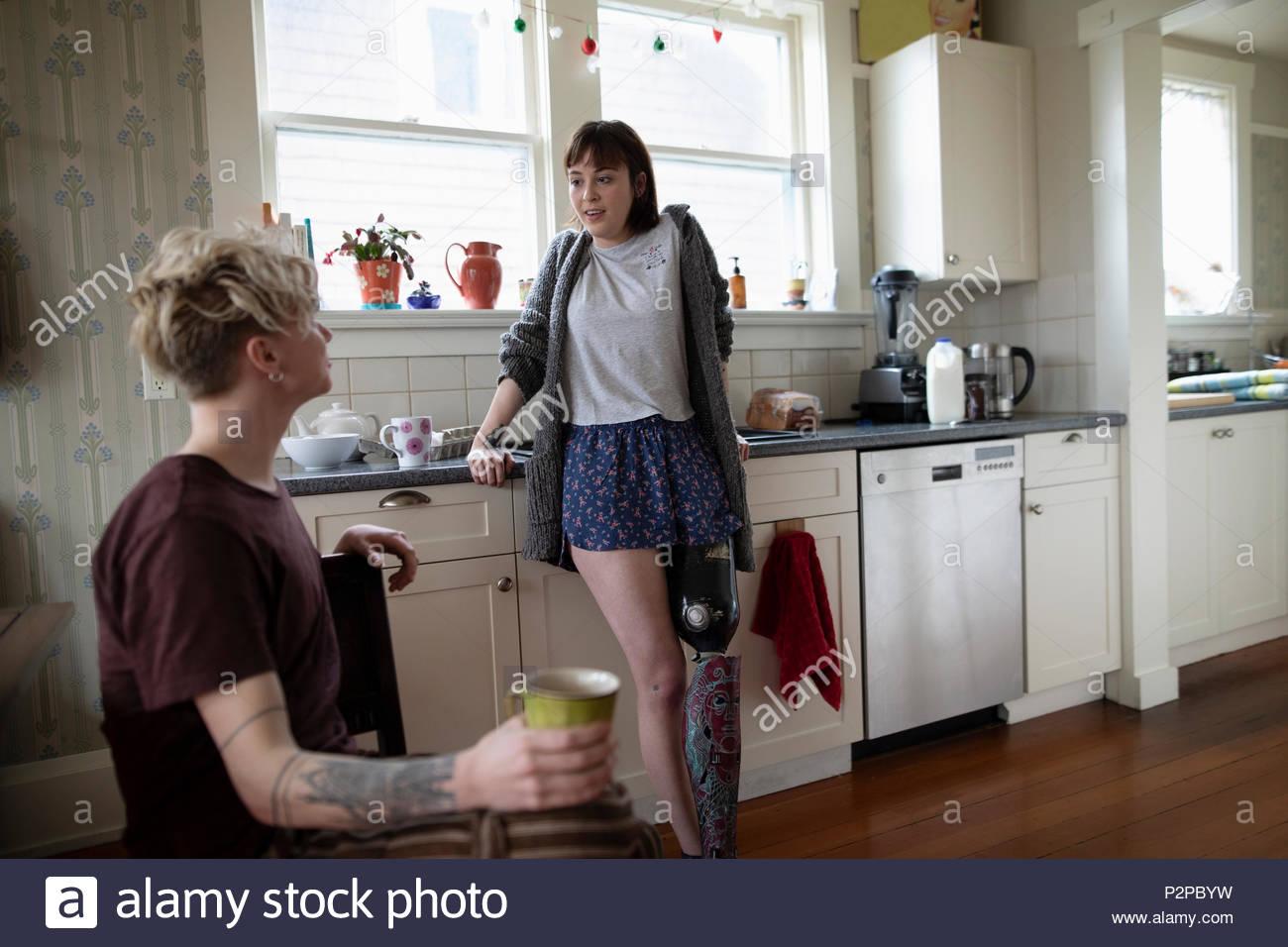 Junge Frau amputee Kaffee trinken, im Gespräch mit Freund in der Küche Stockbild