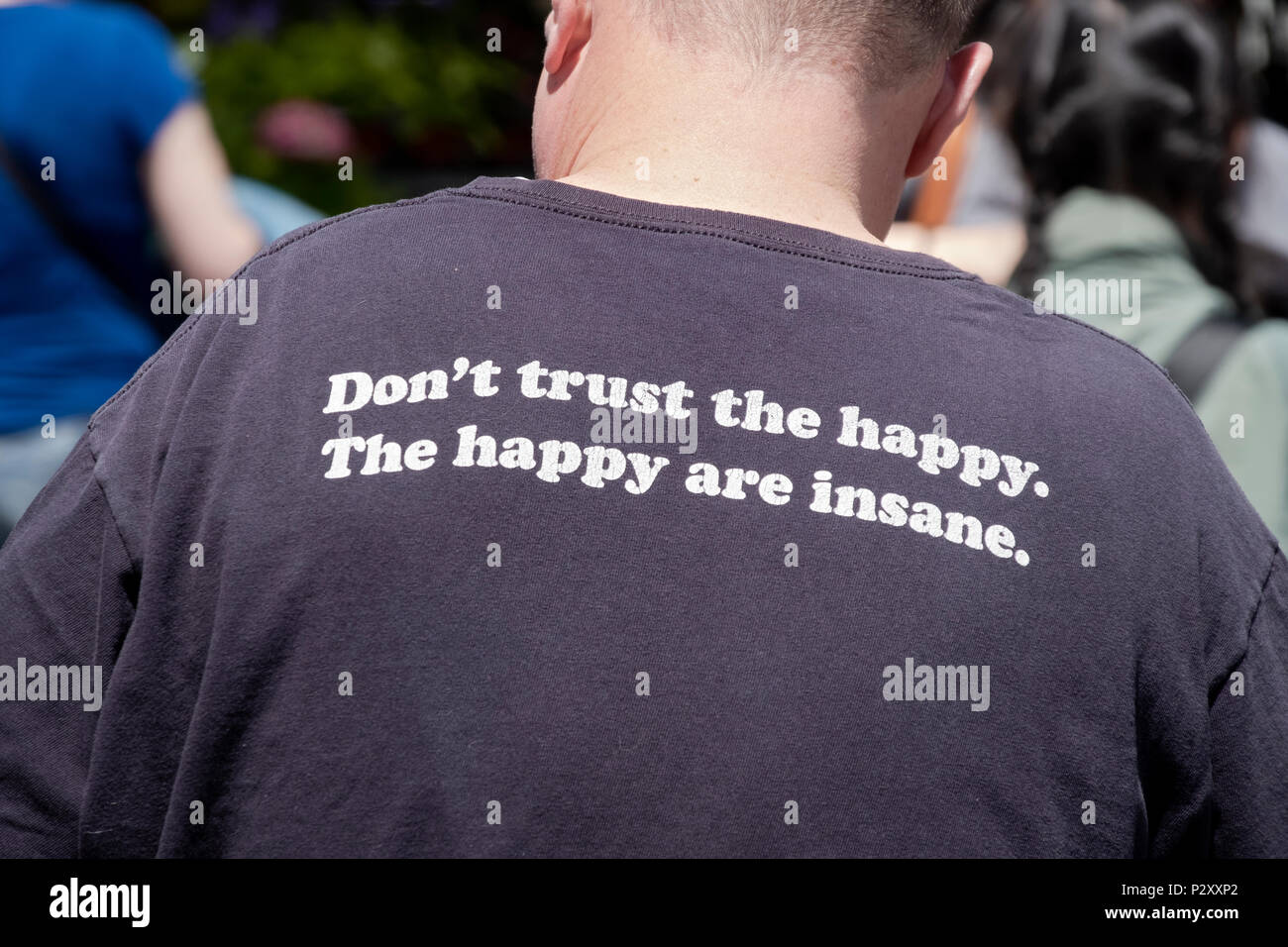 Eine lustige Nachricht auf dem Rücken eines t-shirt, dass glückliche Menschen verrückt und nicht vertrauenswürdig. In Lower Manhattan, New York City. Stockbild