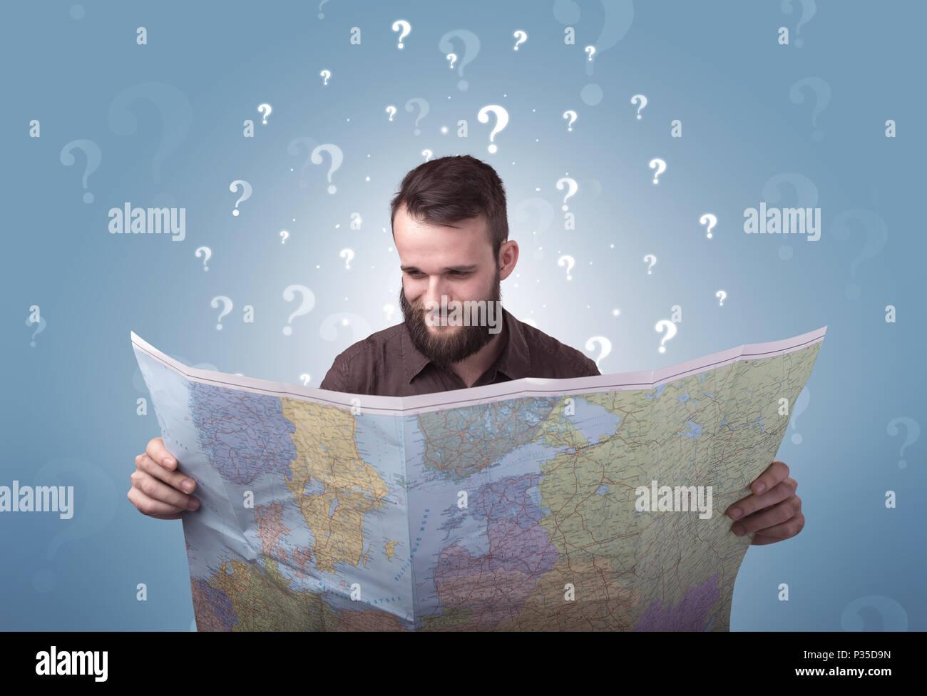 Hübscher junger Mann hält eine Karte mit weißen Fragezeichen über seinem Kopf Stockbild