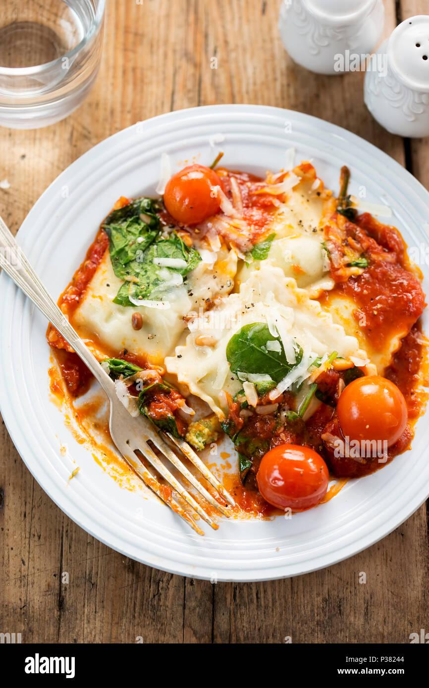 Spinat und Ricotta gefüllte Ravioli in Tomatensauce mit Cherry Tomaten, Pecorino Käse und Pinienkernen Stockbild