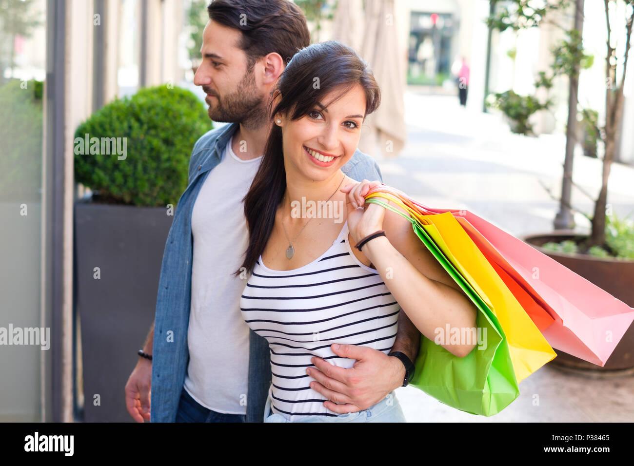 Fröhlicher junger Paare zusammen Einkaufen in der Stadt Spaß Stockbild
