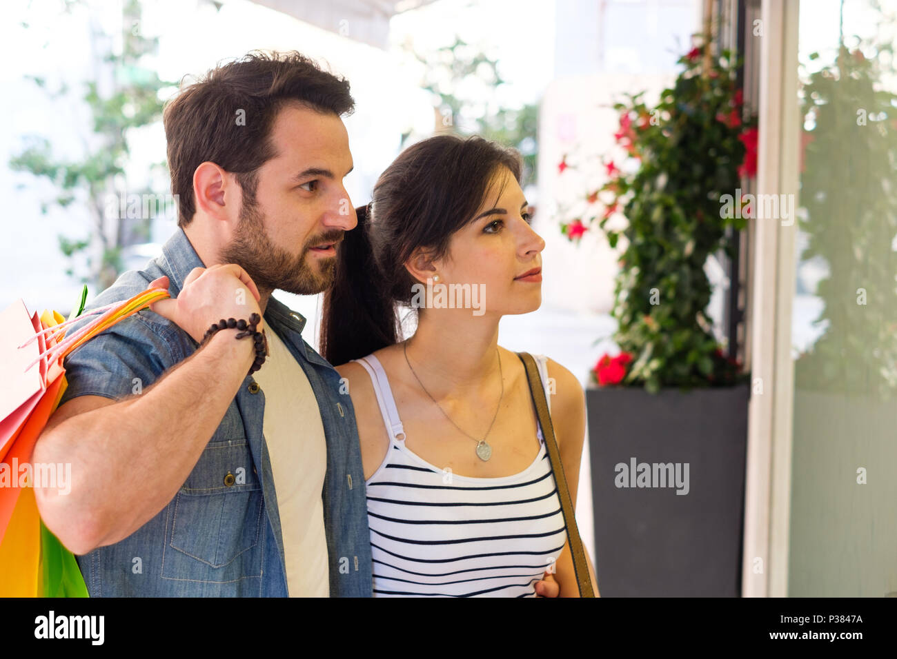 Junge glückliches Paar mit Einkaufstüten während der saisonalen Verkäufe Stockbild
