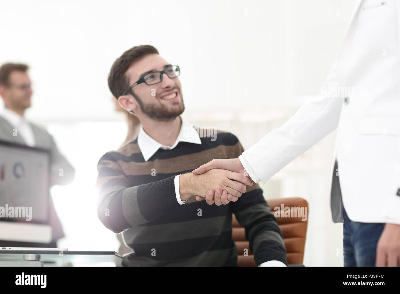 Handshake zwischen Kollegen am Arbeitsplatz Stockbild