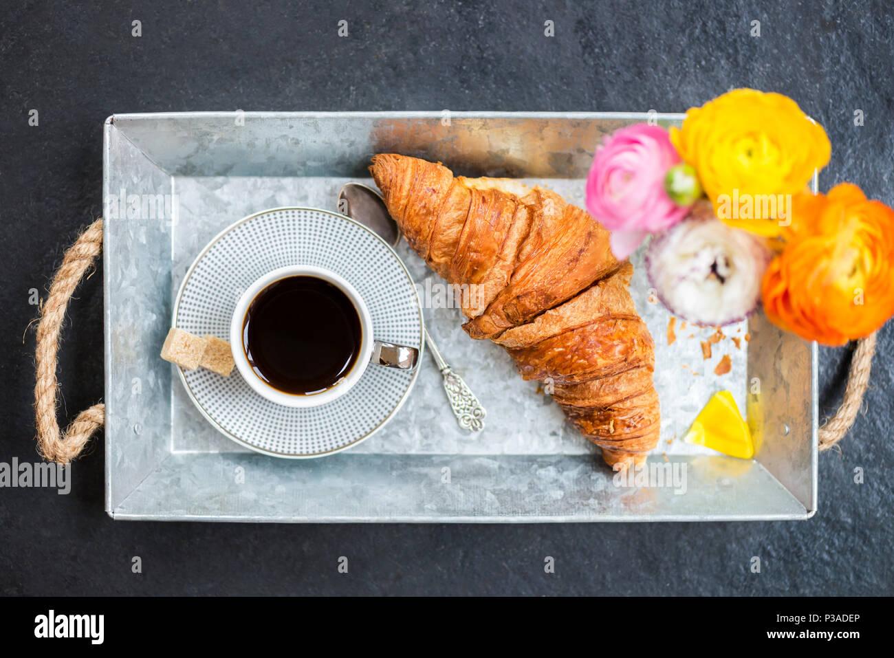 Leichtes Frühstück aus frischen Croissant und Kaffee auf der grauen Fach, Ranunculus Blumen in der Nähe Stockfoto