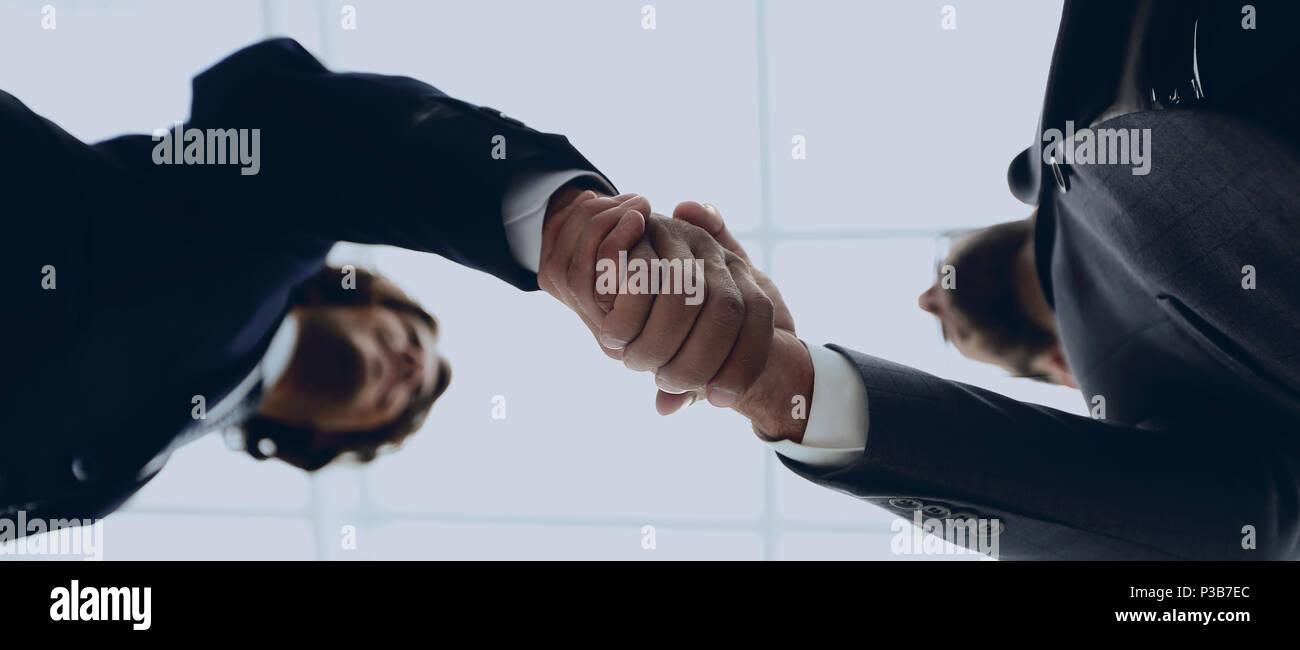 Zwei Geschäftsleute halten sich an den Händen, um die Zusammenarbeit von Unternehmen. Stockbild