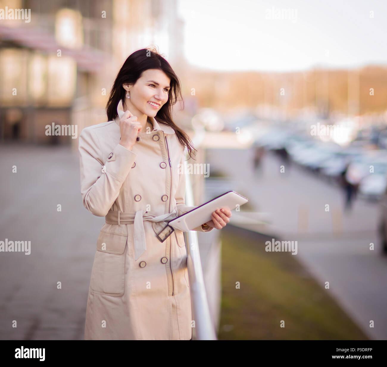 Die moderne Geschäftsfrau, die auf einem digitalen Tablet, neben einem Bürogebäude Stockfoto
