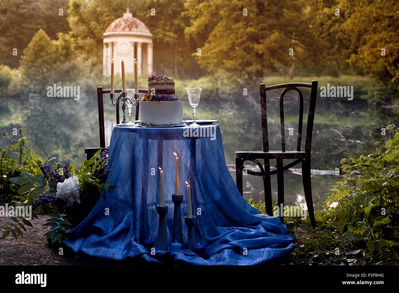 Romantische Hochzeit Abendessen, im Park am Wasser. Viel Grün. Stockbild
